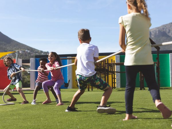 Rear view of multi ethnic group of school kids playing tug of war in playground